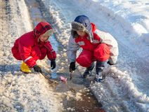 Two boys playing with boat an the creek. Two boys in rainboots playing with paper boat an the creek of melting snow at sunny spring day, outdoors stock photo