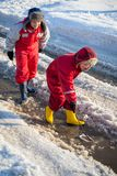 Two boys playing with boat an the creek. Two boys in rainboots playing with toy boat an the creek of melting snow at sunny spring day, outdoors stock photography