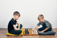 Two boys playing chess at home on the floor. stock photo