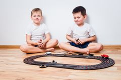 Two boys playing with a children`s road stock photos
