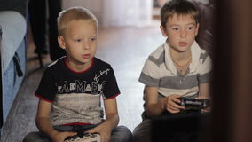 Two boys playing computer games sitting  at home stock video