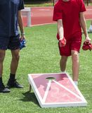 Two boys playing corn hole stock images