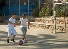 Two boys  playing football. Teenage boys playing soccer at sunny day Stock Images