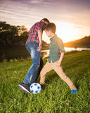 Two boys playing football in the field Royalty Free Stock Photos