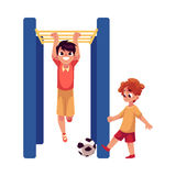 Two boys playing football and hanging on monkey bar at playground Royalty Free Stock Photos