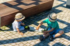 Two boys playing on the ground. royalty free stock image