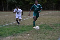 Two boys playing high school soccer stock images