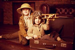 Children in vintage style. Two boys are playing at home to travelers. Childhood. Fantasy, imagination stock images