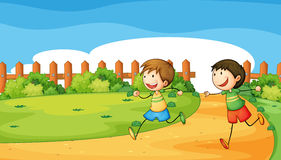 Two boys playing inside the wooden fence Stock Photos