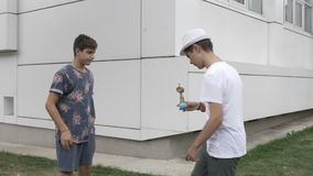Two boys playing with one kendama outdoor -. Two boys playing with one kendama outdoor stock footage