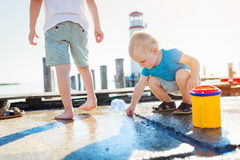 Two boys playing on the pier, lighthouse, sunny summer Stock Images