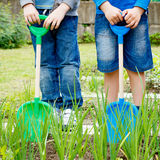 Two boys playing with plastic shovels in the garden. At summer day stock photo