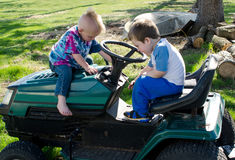 Two boys playing with riding mower Stock Photo