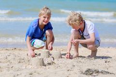 Two boys playing with sand on the beach. Two happy children, twin brothers, blonde school boys playing on the beach building sand castles on a sunny summer day Stock Images