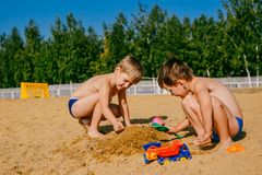 Two boys playing in the sand. Summer at the beach stock photo