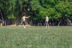 Two boys playing soccer in the afternoon stock photography