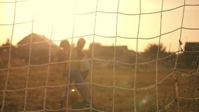 Two boys playing soccer at sunset. A soccer ball is hitting. Football goal. Children`s dreams of victories