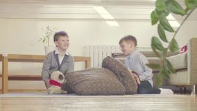 Two boys playing stuffed toys and cushions stock footage