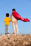 Two boys playing superheroes on the sky stock photo