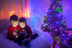 Two boys, playing on tablet at home, next to christmas tree Royalty Free Stock Photography