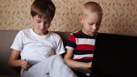 Two boys playing  on a tablet and a laptop at home stock video footage