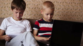 Two boys playing on  a tablet and a laptop at home stock footage