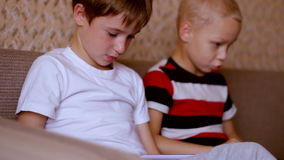 Two boys  playing on  a tablet and a laptop  at stock video footage