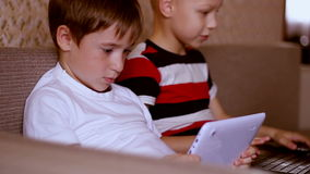 Two  boys playing on a tablet and a laptop at home. Two boys playing on a tablet and a laptop at home sitting on the couch stock footage