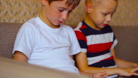 Two boys playing on a tablet  and a laptop at stock footage