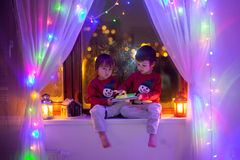 Two boys, playing on tablet on the window Stock Photography