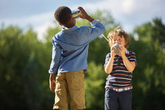 Two boys playing tin can telephone. And having fun at the park Stock Photos