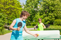 Two boys playing together ping pong outside Stock Photo