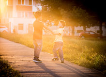 Two boys playing together on street Royalty Free Stock Photography