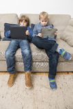 Two boys playing video games on a tablet computer. Two boys, playing games on electronic tablets, slouching on a couch, being bored, and acting individualistic Stock Image