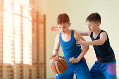 Two boys playng backetball. Two boys playing backetball in the gym Stock Images