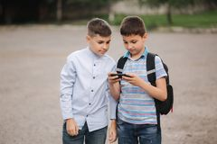 Two boys plays online games after school classes. Young boys smile and use phone royalty free stock photography