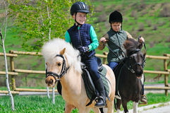 Two boys with ponies Stock Images