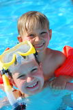 Two Boys in Pool. Two smiling young boys swim together in pool.  One boy is wearing yellow snorkeling goggles Stock Photo