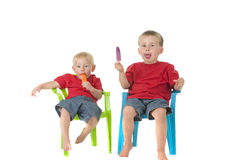 Two boys with popsicles on lawn chairs Royalty Free Stock Image