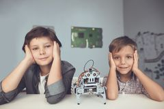 Two boys are posing at a gray table. Between them is a gray robot. The boys sit propped on their heads with their hands. They are smiling Stock Photo