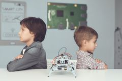 Two boys are posing at a gray table. Between them is a gray robot. The boys turned away from each other and sit with folded arms on their chests Stock Photo