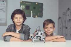 Two boys are posing at a gray table. Between them is a gray robot. The boys sit with folded arms on the table and smile Royalty Free Stock Images