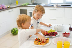 Two boys preparing breakfast in white kitchen Royalty Free Stock Images