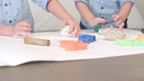 Two boys preparing dough for cookies together with their mum stock photography