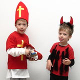 Two boys presenting Saint Nicholas with gift stocking and little devil Stock Images