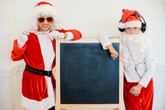 Two boys pretending he is a Bad Santa near black board Royalty Free Stock Images