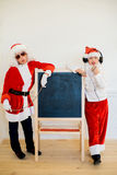Two boys pretending he is a Bad Santa near black board Royalty Free Stock Photos