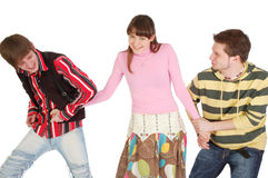 Two boys pull girl in different directions by the Stock Image