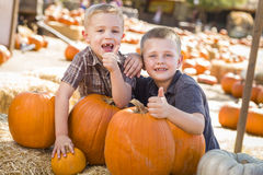 Two Boys at the Pumpkin Patch with Thumbs Up Royalty Free Stock Images