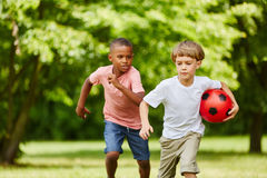 Two boys racing in the park. With soccer ball in summer royalty free stock photography